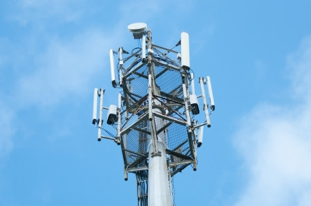 microwave antenna: Cell  phone tower rises against a blue sky. Stock Photo