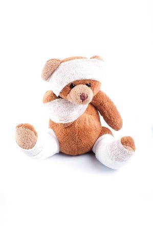 Ziek teddybeer verpakt in verbanden, geïsoleerd op witte achtergrond