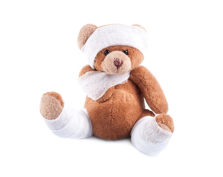 Sick teddy bear wrapped in bandages, isolated on white background photo