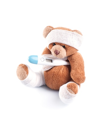 Sick teddy bear wrapped in bandages with underarm thermometer, isolated on white background photo