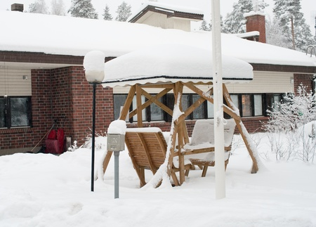 Winter cottage and pergola covered by snow   in Finland Stock Photo - 9860518