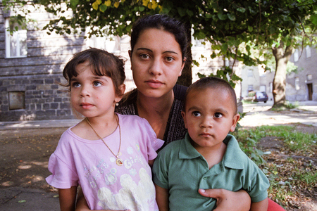 PREROV, CZECH REPUBLIC, JUNE 25, 2011: Charming and poor Gypsy family in the ghetto street Skodova, now defunct ghetto was razed. Photographed on cine-film, photo has a characteristic noise, Europe Editorial