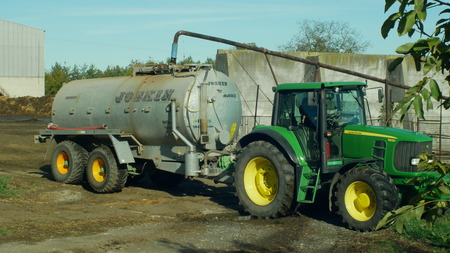 OLOMOUC, CZECH REPUBLIC, AUGUST 21, 2018: Tractor John Deere special trailer spreading fertilizer of slurry on field farming, tanking of liquid dung healing from cows, fertilization slurry important Editorial