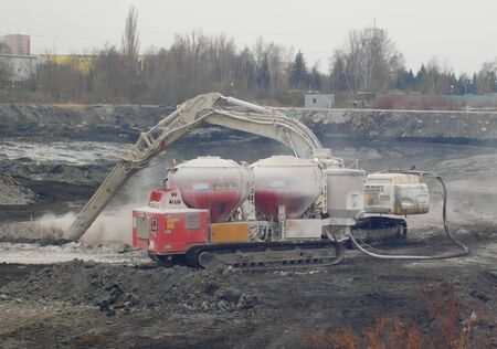 OSTRAVA, CZECH REPUBLIC, NOVEMBER 28, 2018: Liquidation of remediation of landfills waste of oil and toxic substances sludge, burnt lime is applied to oil pollution by means of fine cutter excavator Sajtókép