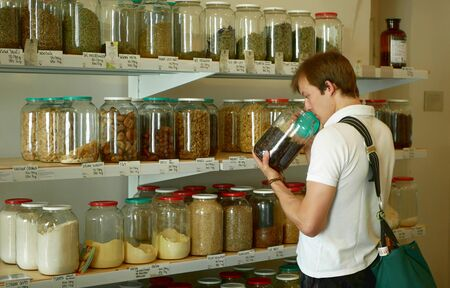 PRAGUE, CZECH REPUBLIC, MAY 30, 2019: Shop without packaging, weight and pay, man nose smell, healthy wide assortment of dried fruits, nuts in jars and glass bottles on their own bags Archivio Fotografico - 129998805