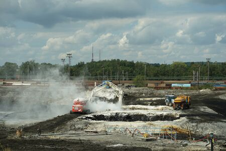 OSTRAVA, CZECH REPUBLIC, NOVEMBER 28, 2018: Liquidation of remediation of landfills waste of oil and toxic substances sludge, burnt lime is applied to oil pollution by means of fine cutter excavator Archivio Fotografico - 129998889