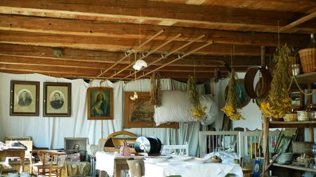 OLOMOUC, CZECH REPUBLIC, SEPTEMBER 5, 2019: Traditional Moravia cottage old folk Hana with table and dried herbs. Interior of peasant bed and clay pots unique hut. Christian paintings Archivio Fotografico - 129998939
