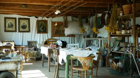 OLOMOUC, CZECH REPUBLIC, SEPTEMBER 5, 2019: Traditional Moravia cottage old folk Hana with table and dried herbs. Interior of peasant bed and clay pots unique hut. Christian paintings Archivio Fotografico - 129998941