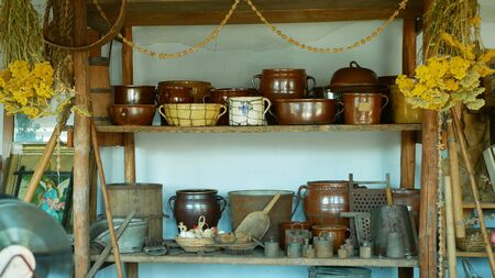 OLOMOUC, CZECH REPUBLIC, SEPTEMBER 5, 2019: Traditional Moravia cottage old folk Hana with pots jar and bottle with burnt clay crockery and dried herbs. Interior of peasant and dishes Archivio Fotografico - 129998937