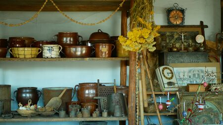 OLOMOUC, CZECH REPUBLIC, SEPTEMBER 5, 2019: Traditional Moravia cottage old folk Hana with pots jar and bottle with burnt clay crockery and dried herbs. Interior of peasant and dishes Archivio Fotografico - 129998942