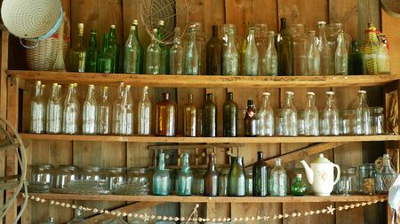 OLOMOUC, CZECH REPUBLIC, SEPTEMBER 5, 2019: Jar bottles with glass and carboy, traditional Moravia cottage old folk Hana. Interior of peasant and dishes glassful unique hut, farmhouse Archivio Fotografico - 129998943