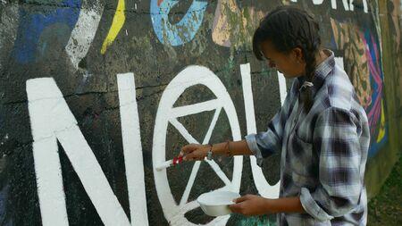 OLOMOUC, CZECH REPUBLIC, SEPTEMBER 22, 2019: Activist woman paints and repainting symbol Extinction Rebellion climate emergency on legal wall for graffiti, action demonstration Archivio Fotografico - 131611720