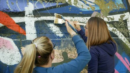 OLOMOUC, CZECH REPUBLIC, SEPTEMBER 22, 2019: Activist people paints and repainting symbol Extinction Rebellion climate emergency on legal wall for graffiti, action demonstration Archivio Fotografico - 131611735