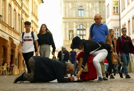 PRAGUE, CZECH REPUBLIC, SEPTEMBER 9, 2019: Homeless begging Asian tourists throw coin money into baseball cap and recalculates money, begs alms kneeling or kneel street life authentic Archivio Fotografico - 132990280