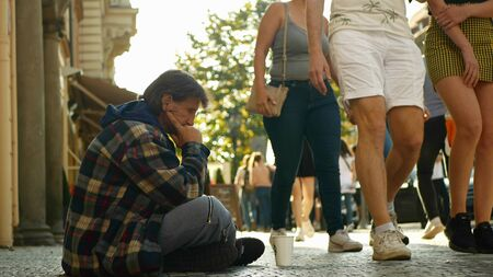 PRAGUE, CZECH REPUBLIC, SEPTEMBER 9, 2019: Homeless begging Asian tourists throw coin money into cup and recalculates money, begs alms kneeling or kneel street life authentic Archivio Fotografico - 132990416