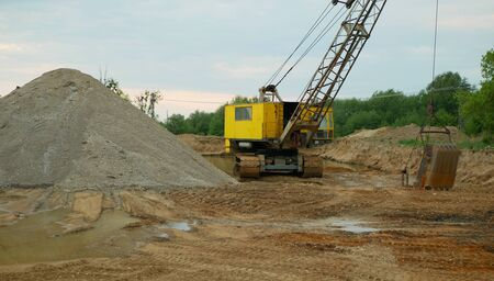 Mining for gravel sand pit excavator or digger machine dredger extraction colliery output of building surface gray pile and mine quarry grit quartz pea ballast road-metal, high quality industry building material, hole devastation of nature and landscape, construstion site, global change, degradation of nature by human activity, construction of highways and towns, Czech Republic, Europe, European Union