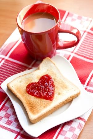 desayuno romantico: rebanada de pan con forma de mermelada de frutas del coraz�n Foto de archivo