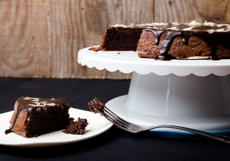 cake stand: A piece of chocolate almond cake on the plate and cake on the stand Stock Photo