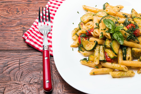 Delicious pasta with sauce,zucchini and tomatoes photo