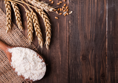 Ears of wheat and flour in the wooden spoon on the table Stock Photo