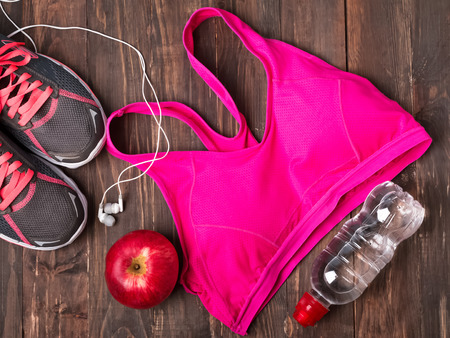 gym shoes: Sport equipment. Sneakers, water, pink top and earphones  isolated on white