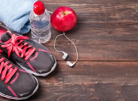 Sport apparatuur. Sneakers, water en oortelefoons op houten Stockfoto