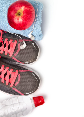 Sport equipment. Sneakers, water, earphones and apple, isolated on white background