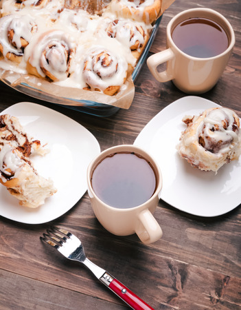 woden: Delicious glazed cinnamon buns and cups with tea in the woden table Stock Photo
