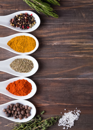 indian spices: Dry spices in spoons and green herbs on the wooden table, top view