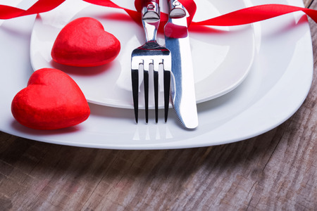 dinner dish: Valentines day table setting concept. Knife and fork on the plate close-up. Stock Photo