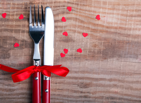 romantic places: Knife and fok and little red hearts on the wooden table. Valentines day table setting.
