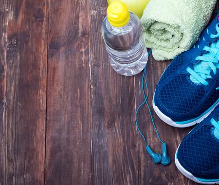 スポーツ機器。スニーカー、水、タオル、木製の背景にイヤホン