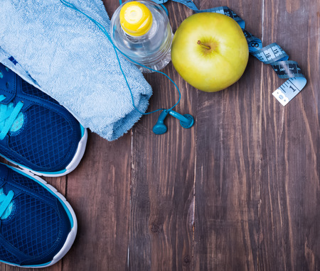 Sport equipment. Sneakers water towel and earphones on the wooden background Stock Photo