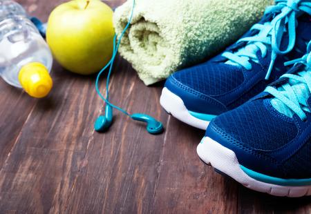 salud y deporte: Equipamiento deportivo primer. Zapatillas de deporte de la toalla del agua y los auriculares en el fondo de madera Foto de archivo
