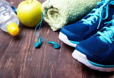 Sport equipment closeup. Sneakers water towel and earphones on the wooden background Standard-Bild