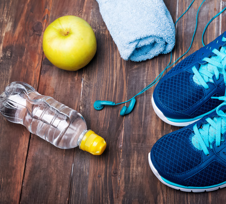 Sneakers water towel earphones and green apple on the wooden background