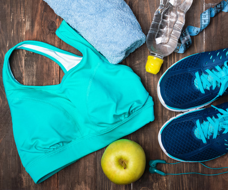 Fitness accessories on the wooden background. Sneakers bottle of water earphones towel and sport top.