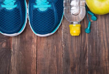 gimnasio mujeres: Equipo de deporte. Auriculares zapatillas de agua y manzana en el fondo de madera vista superior Foto de archivo