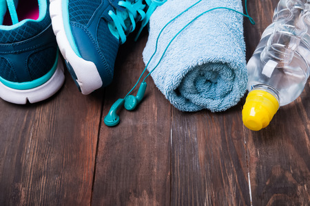 Sport equipment. Sneakers water towel and earphones on wooden background