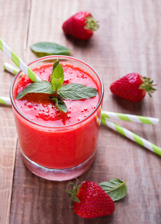 red straw: Strawberry smoothie on the wooden table closeup