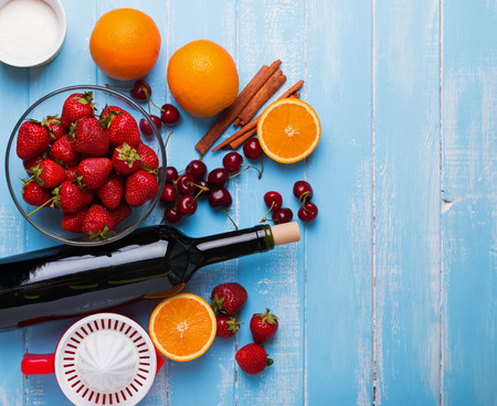 Ingredients for sangria. Bottle of wine, berries, oranges, squeezer on the wooden table, top view Stock Photo