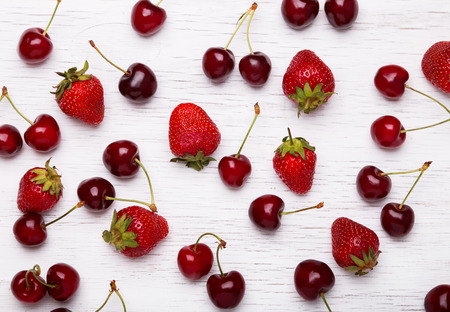 cherry: Fresh cherries and strawberries on the white wooden table, top view