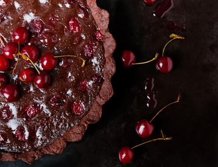 ganache: Delicious tart with dark chocolate ganache and cherries. Top view, dark toned photo. Stock Photo