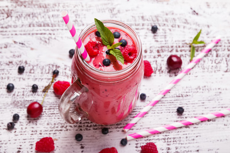 Summer berries smoothie in a glass mug close-up