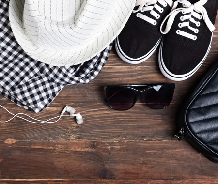 Modern girl outfit on the wooden background, top view. Checkered shirt, hat, black-and-white gumshoes, sunglasses.