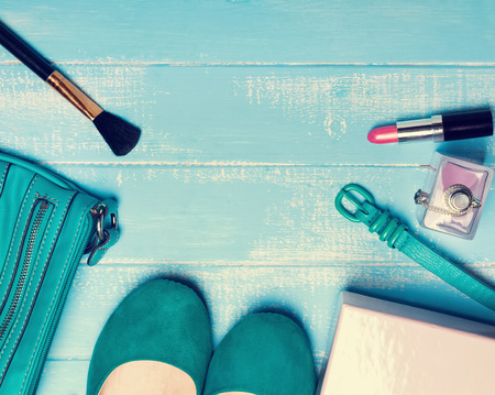 photo of accessories: Woman accessories of turquoise and pink color. Flat shoes, belt, bag and cosmetics. Retro toned photo.