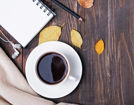 Autumn still life. Coffee, notepad, pensil and leaves on the wooden background, top view.