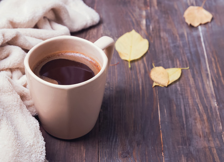 yellow: Autumn mood. Coffee, leaves and blanket on the wooden background close-up Stock Photo