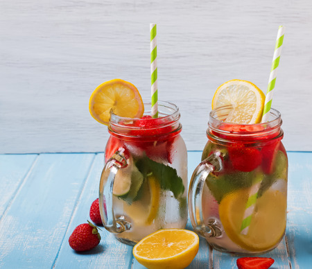 Strawberry detox water in glass jars on blue colored tablle Stock Photo