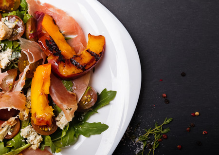 grill: Delicious salad with grilled peaches, prosciutto and cheese in white plate on black board top view Stock Photo